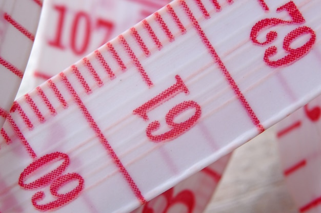 Tailor measuring tape with red numbers.