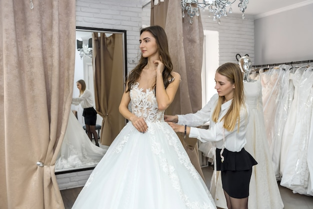 Tailor measuring wedding dress on bride in store