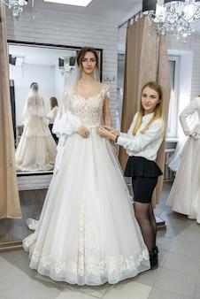 Портной измерения свадебного платья на невесте в магазине