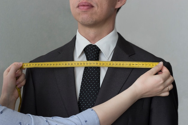 Tailor removes the measurements from the jacket of a man