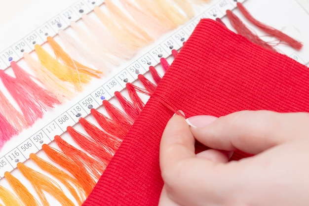 Tailor selects the color of the thread in the catalog for the red fabric. atelier shop of fabrics and accessories.