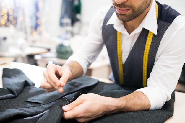 Tailor sewing jacket closeup