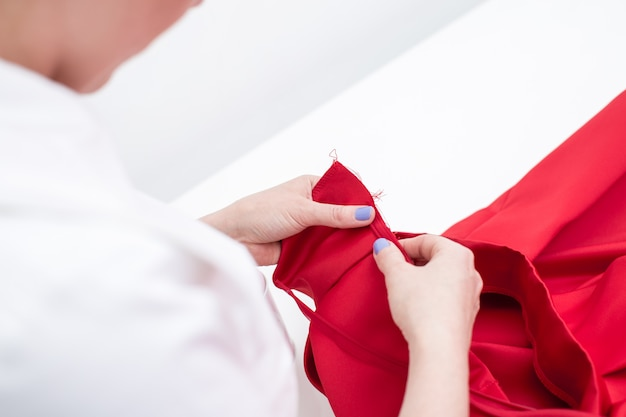 Tailor sews red dress