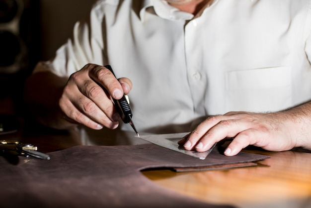 Tailor sketching on the leather tissue. high quality photo