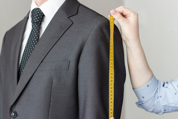 The tailor takes measurements from the suit, white background, isolated