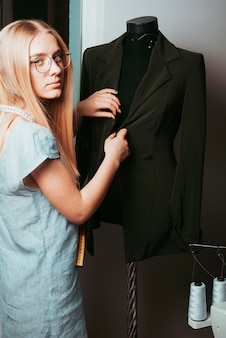 Tailor touching jacket on mannequin