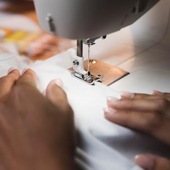 Портной, используя крупный план швейной машины