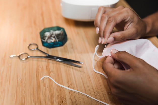 Tailor using a needle to make a fabric mask