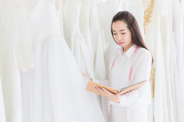 The tailor who owns the boutique is checking the number of wedding dresses in the shop.