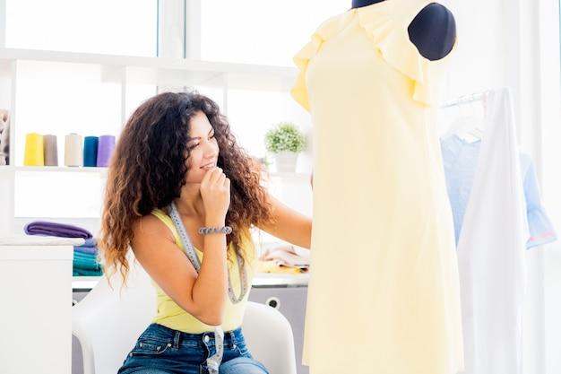 Портной с манекеном в платье в швейной ателье