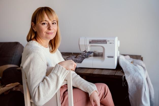 Портной женщина и ее швейная машина сзади