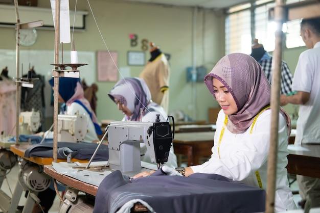 仕事でミシンを使用して首に巻尺を着用してヒジャーブの女性を仕立てる