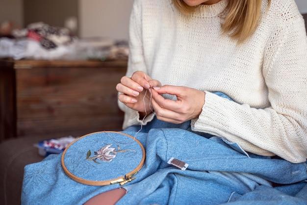 직물 바느질 도구를 사용하여 여자를 재단사
