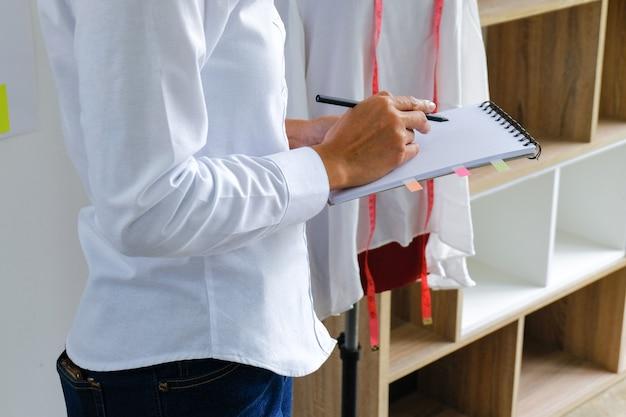 テーラーショップで働くテーラーウーマンワークショップスタジオでスタイリッシュなファッションデザイナーテーラー新しいコレクションをデザインする洋裁とクリエイティブなファッションコレクションのコンセプト
