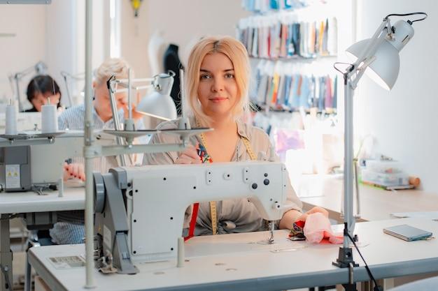 機械の後ろの縫製で働く仕立て屋
