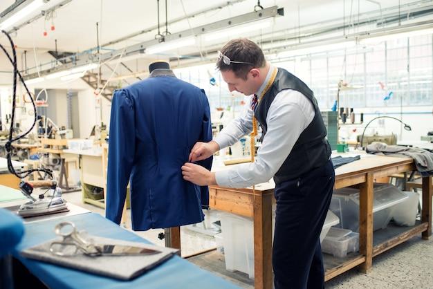 Tailor working on jacket in workshop