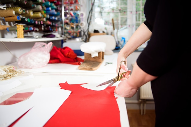 Портной работает с тканью за столом в ателье.