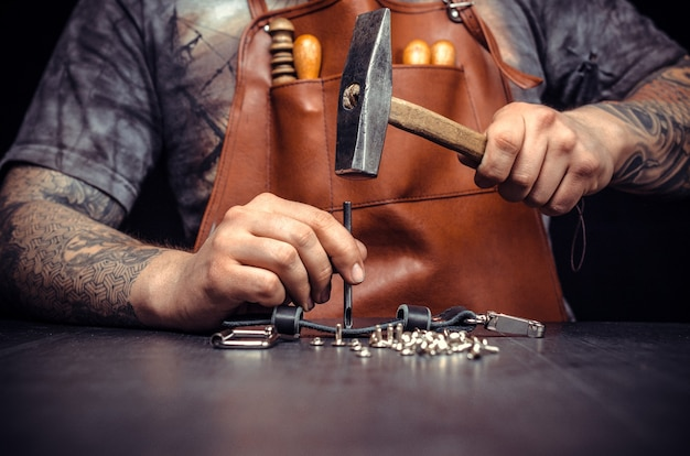 Tailor workplace with pieces of leather and rivets.