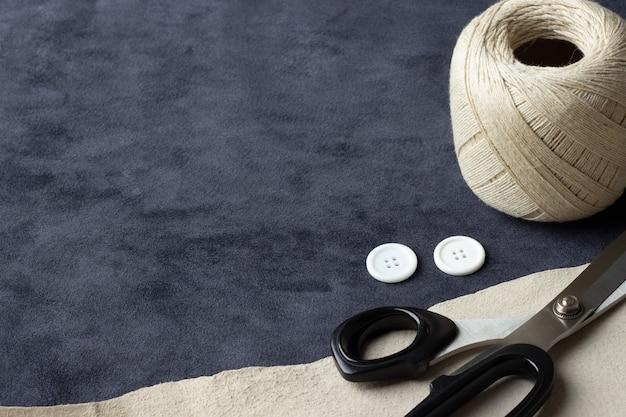 仕立てのコンセプト。ダークブルーとベージュの革の背景にミシンアクセサリー。