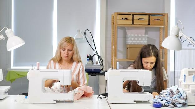Пошив одежды. швея за работой в цехе шьет одежду на швейной машине. портнихи шьют одежду в ателье. две женщины-швеи. пошив одежды в швейном деле.