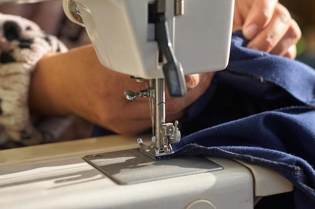 仕立て工程-彼女の縫製の後ろの女性の手