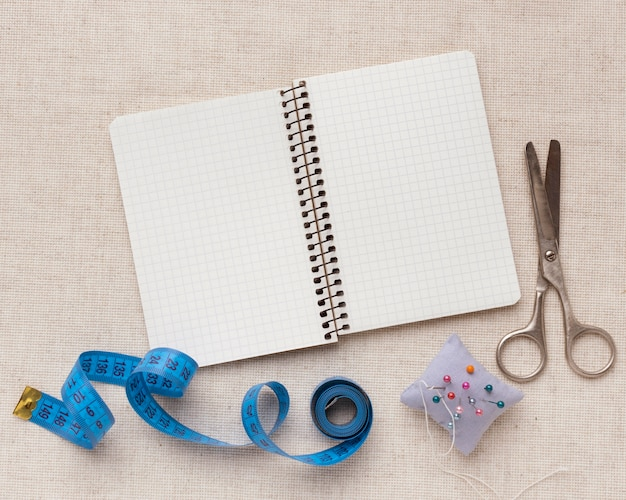 Tailoring tools and elements assortment with empty notebook