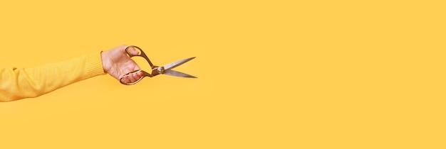 노란색 배경 위에 손에 재단사 가위