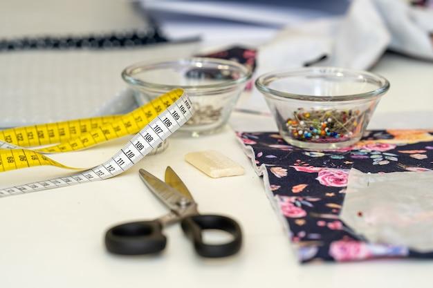 仕立て屋の縫製テーブルで巻尺を仕立てる
