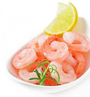 흰 그릇에 신선한 레몬과 로즈마리와 새우의 꼬리
