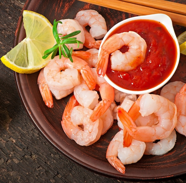 Tails of shrimps with fresh lemon and rosemary in plate