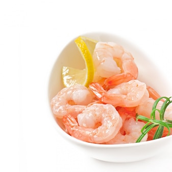 Tails of shrimps with fresh lemon and rosemary in a white bowl
