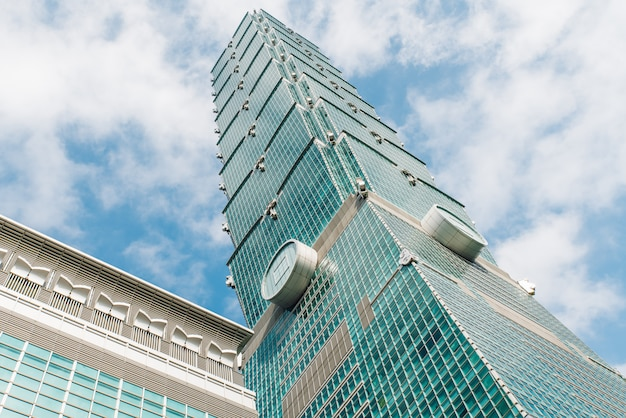 Taipei 101 building from below with bright blue sky and cloud in taipei, taiwan.