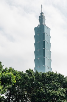Taipei 101 building with tree branches below with bright blue sky and cloud in taipei, taiwan.