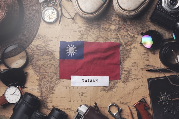 Taiwan flag between traveler's accessories on old vintage map. overhead shot