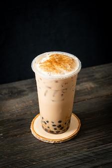 Тайваньский молочный чай с пузырями и сыром, обожженный на деревянном столе