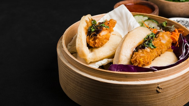 Taiwan's traditional food gua bao in steamer against black background