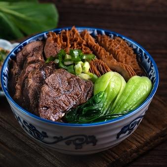 Тайваньский знаменитый суп с лапшой из говядины с нарезанной тушеной говяжьей рулькой, рубцом и овощами на поверхности деревянного стола.