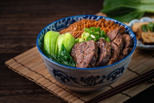 Taiwanese famous food beef noodle with sliced braised beef shank, tripe and vegetables on wooden table background.