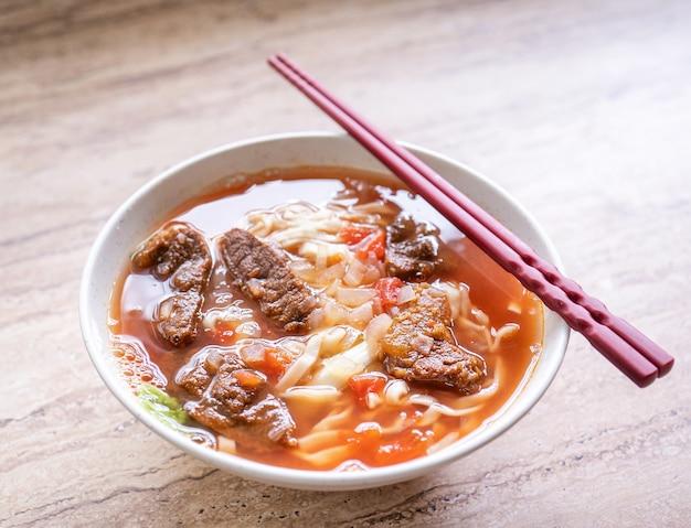Тайваньская кухня - рамен с говядиной и лапшой в миске с томатным соусом