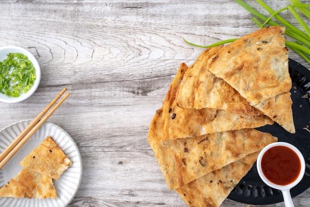台湾料理-明るい木製のテーブルの背景においしいフレーク状のネギのパイのパンケーキ、台湾の伝統的なスナック、上面図。