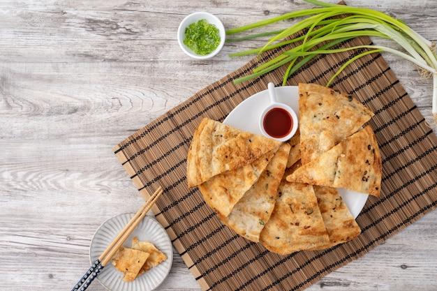 明るい木製のテーブルに台湾料理おいしいフレーク状のネギのパイのパンケーキ