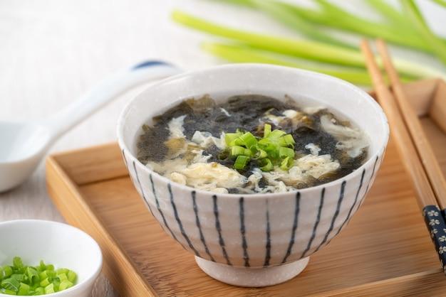 Тайваньская еда - домашний вкусный суп из яичных капель из морских водорослей в миске на подносе на светлом фоне деревянного стола.