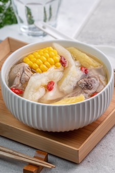 Taiwanese homemade delicious chicken soup food in a bowl with pineapple, bitter gourd and sweet corn on cement gray table