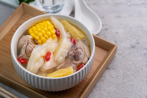 Тайваньский домашний вкусный куриный суп в миске с ананасом, горькой тыквой и сладкой кукурузой на цементно-сером столе