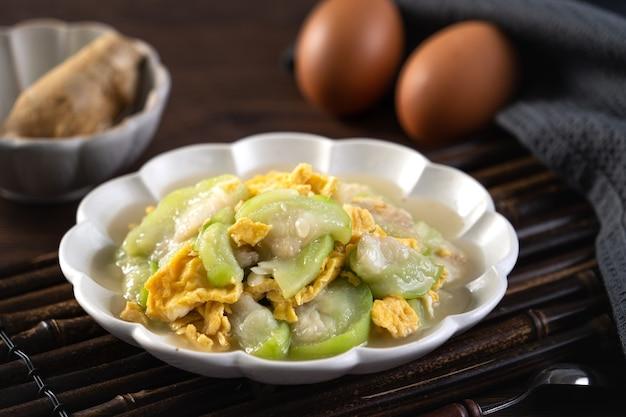 素朴なテーブルの背景のプレートにヘチマひょうたんとごま油を添えたスクランブルエッグの台湾の自家製郷土料理。