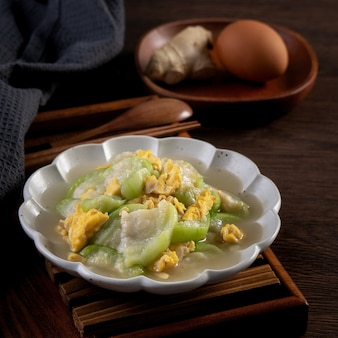Taiwanese homemade scrambled eggs with loofah gourd and sesame oil in a plate on rustic table