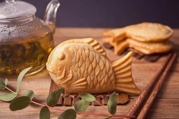 たいやき日本の屋台の魚の形をした甘いワッフルの木製テーブル