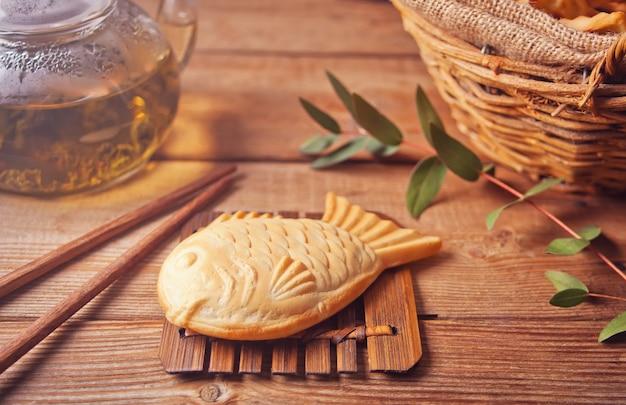 Taiyaki japanese street food fish-shaped sweet filling waffle on wooden table