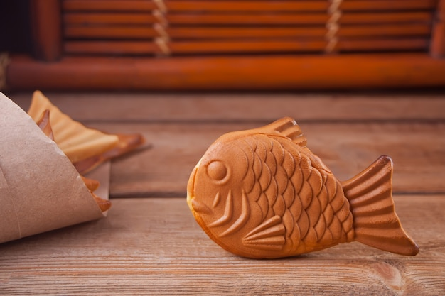 Taiyaki japanese street food fish-shaped sweet filling waffle on wooden table.