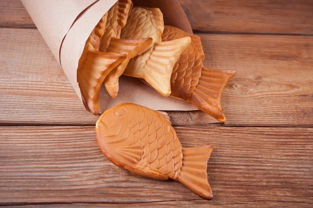 Японская уличная еда taiyaki в форме рыб сладкой вафельной начинкой на деревянный стол.